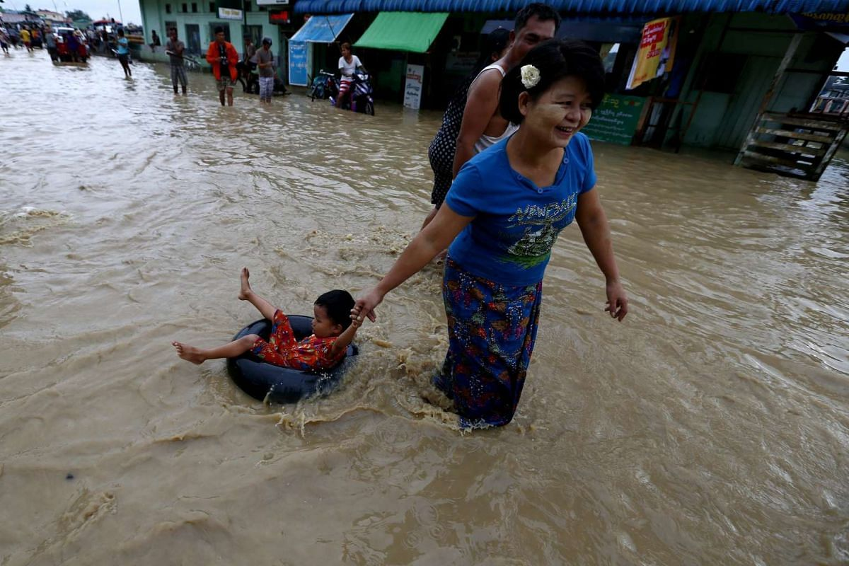 A woman pulling a child on a rubber tube through floodwaters in Pathein, Myanmar,  on Aug 12.