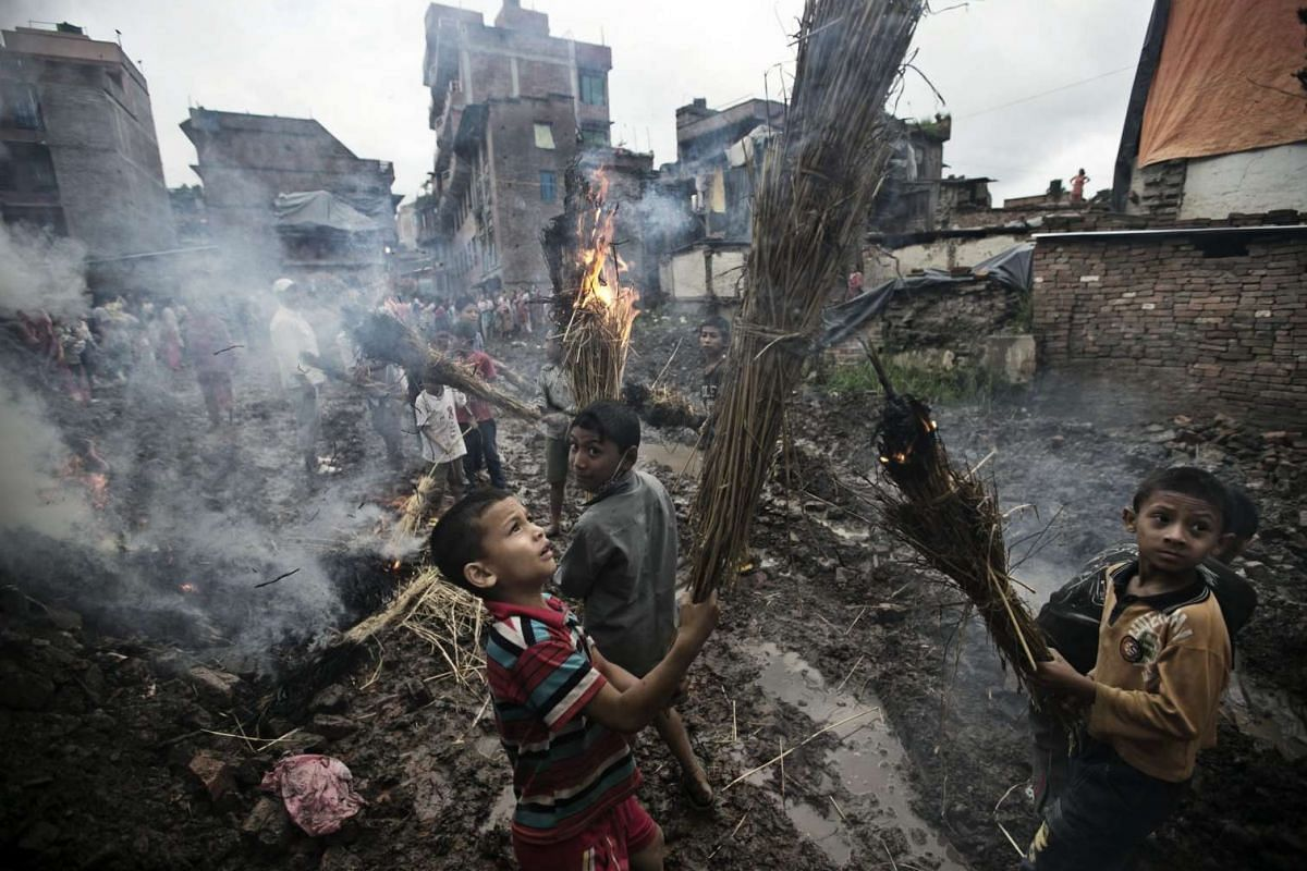 Children playing near a burnt straw effigy of the mythical demon Ghanta Karna during the Hindu festival Gathemangal in Bhaktapur, Nepal,  on Aug 12.