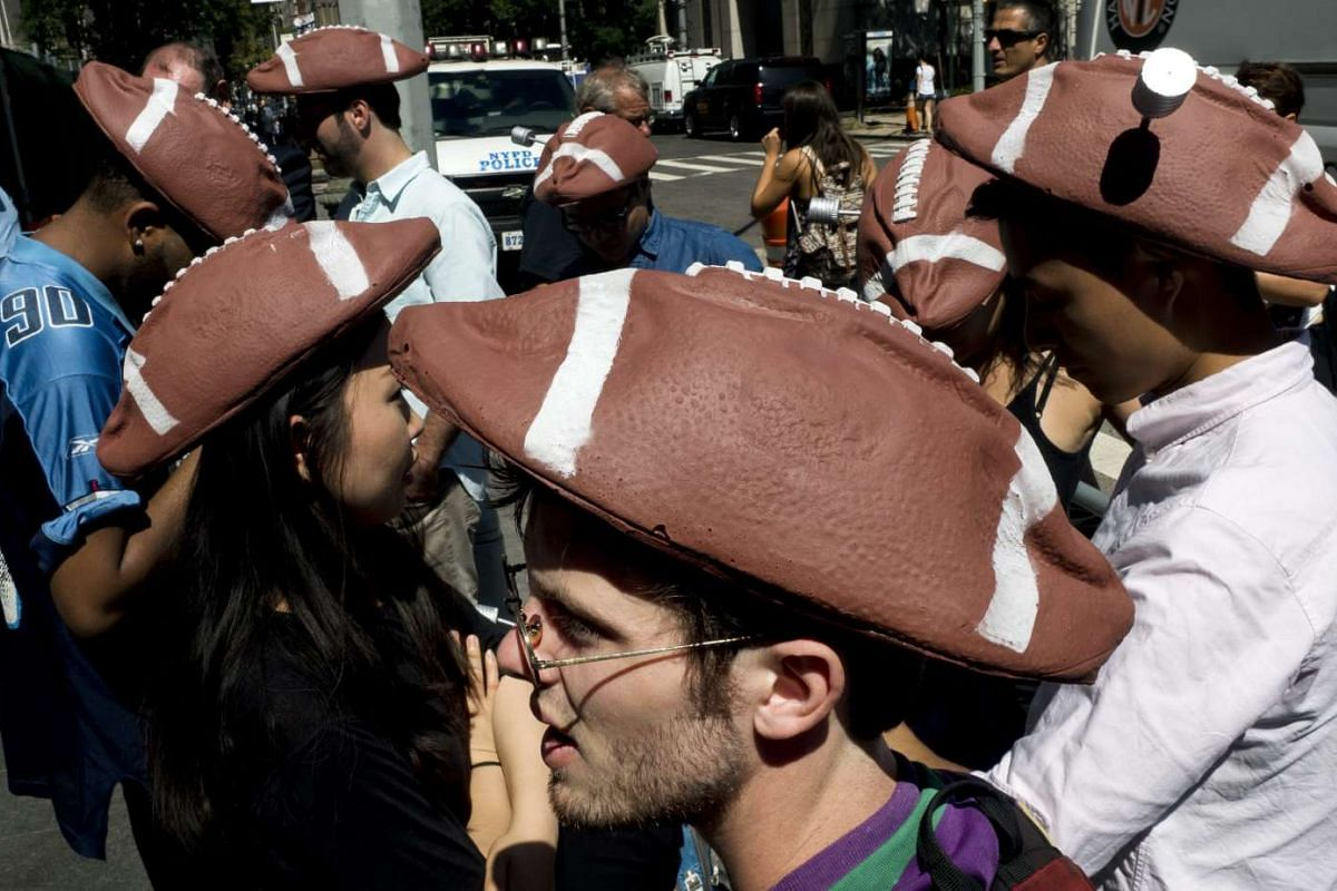 People wearing hats that look like deflated footballs outside the US Federal Courthouse in New York before a hearing about American football player Tom Brady's appeal against a four game suspension on Aug 12.