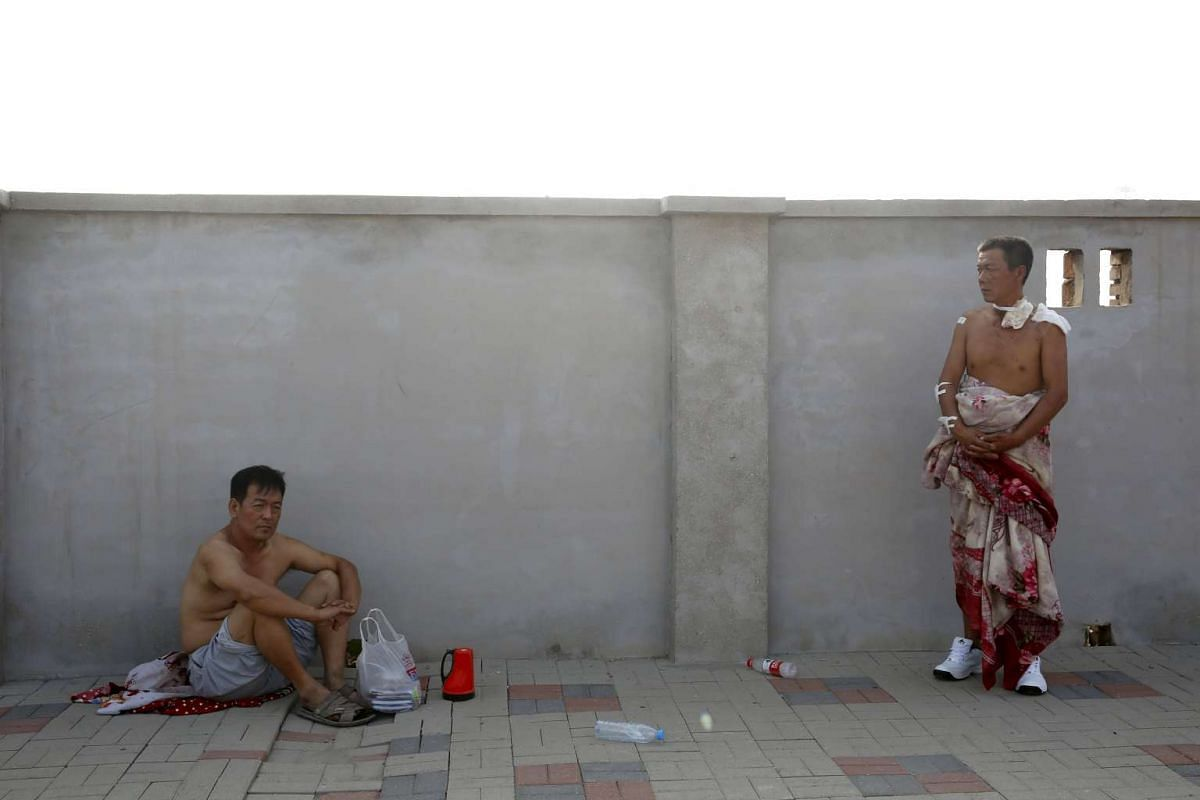 An injured man (right) looks on near the site of the explosions at the Binhai new district in Tianjin, China, Aug 13, 2015.