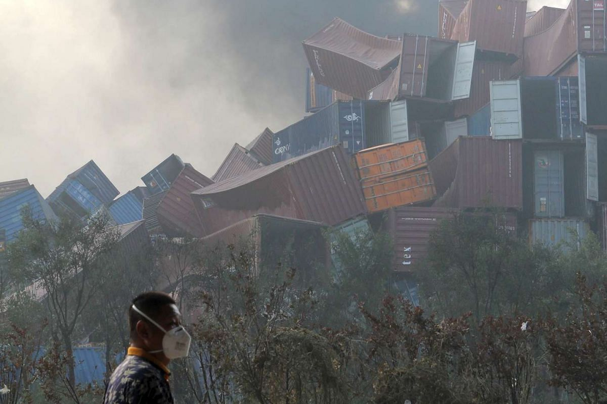 A man wearing a mask walks past overturned shipping containers after explosions hit the Binhai new district in Tianjin on Aug 13, 2015.