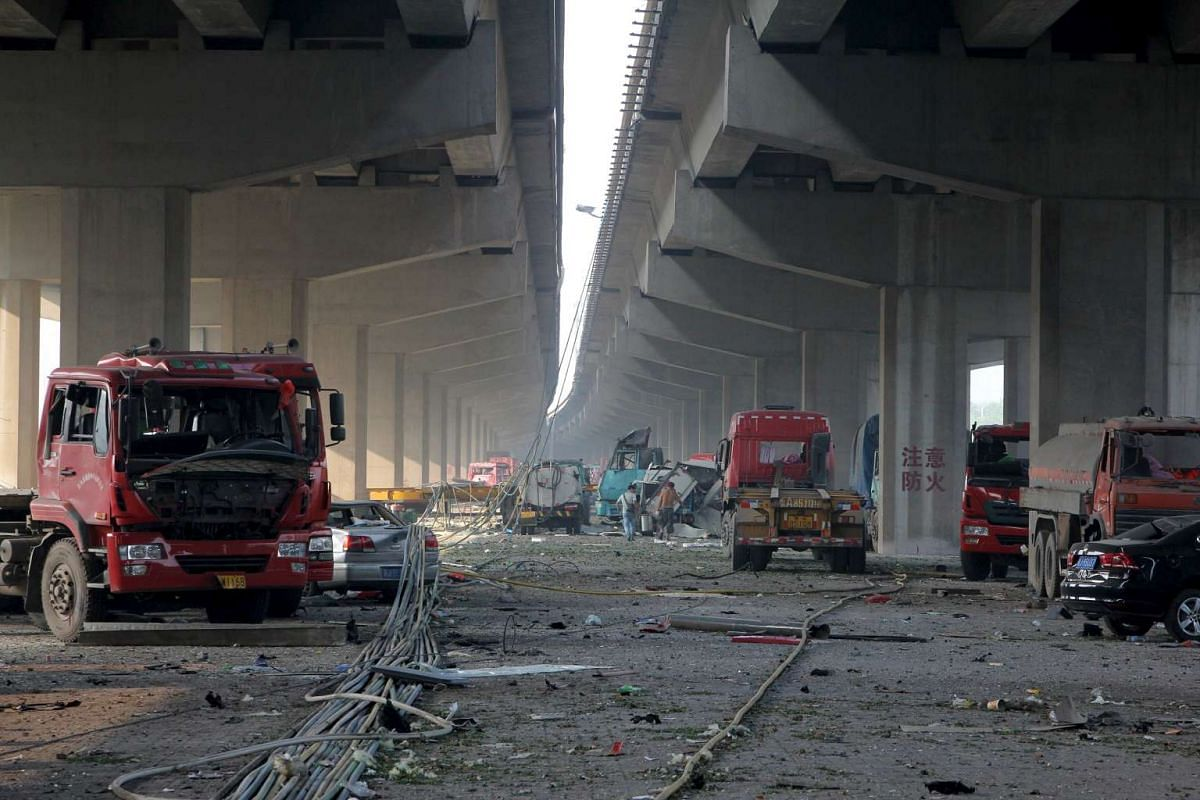 Damaged vehicles are seen under bridges close to the site of the explosions at Binhai new district, Tianjin on Aug 13, 2015.
