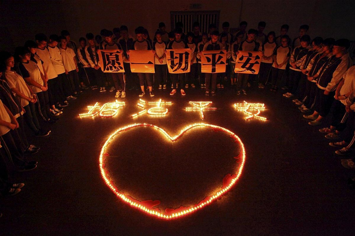 """Students and teachers standing around candles which form into Chinese characters """"Tanggu be safe"""" and a heart shape, during a candlelight vigil for victims of the explosions in Tianjin on Wednesday night, at a school in Zhuji, Zhejiang province, Chin"""