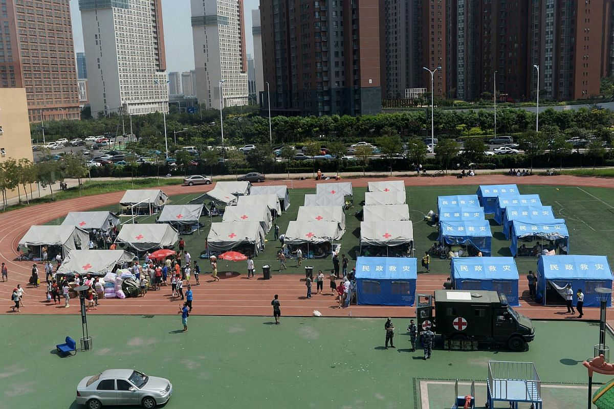 People putting up tents in a temporary shelter at an elementary school in Tianjin on Aug 13, 2015.