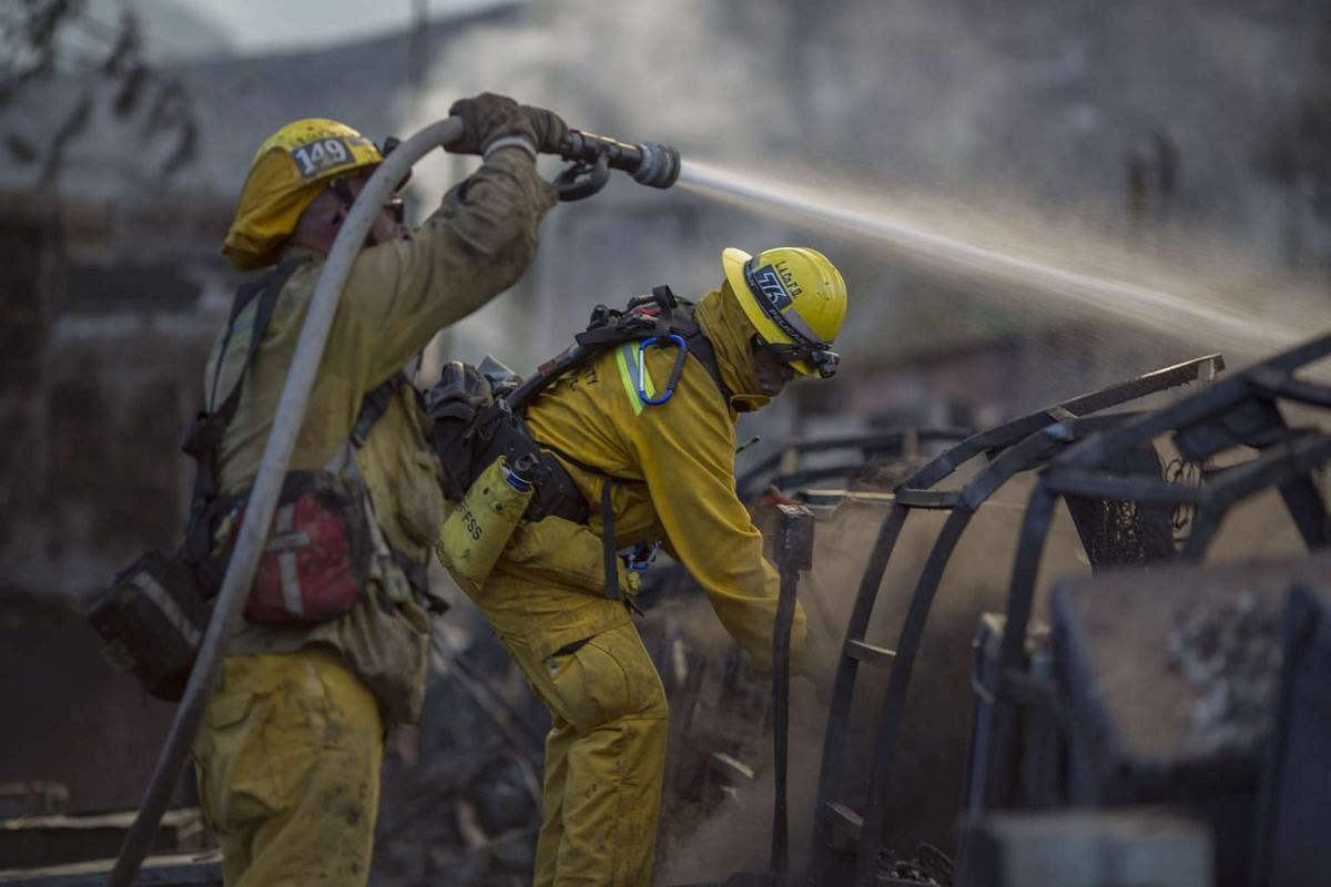 Firefighters hosing down the smoldering ruins of a building at the Warm Springs Rehabilitation Center at the Warm Fire on Aug 16, 2015 in the Angeles National Forest north of Castaic, California. The wildfire has burned six structures and blackened 5