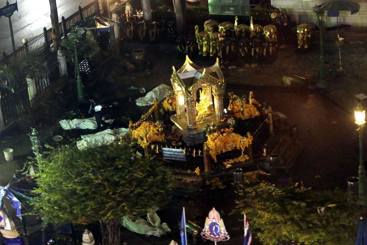 A general view taken from a moving train shows bodies covered in white sheets around the Erawan Shrine, central Bangkok, Thailand, Aug 17, 2015.