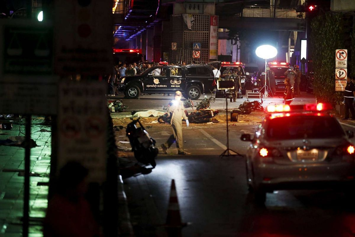 The body of a victim covered with a sheet lying in the street as security forces and emergency workers gather at the scene of the blast in central Bangkok on Aug 17, 2015.