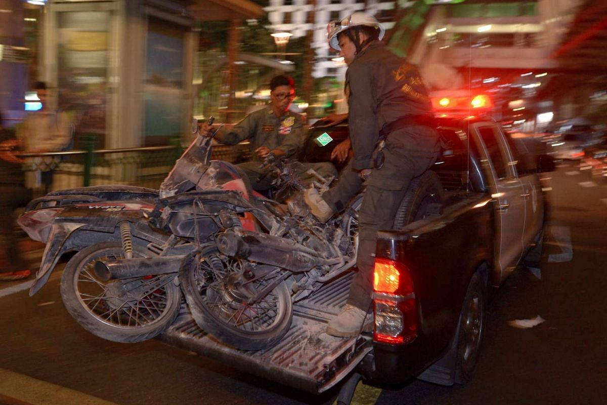 Thai rescue workers transport damaged motorcycles from the scene of a bomb blast outside a religious shrine in central Bangkok late on Aug 17, 2015.