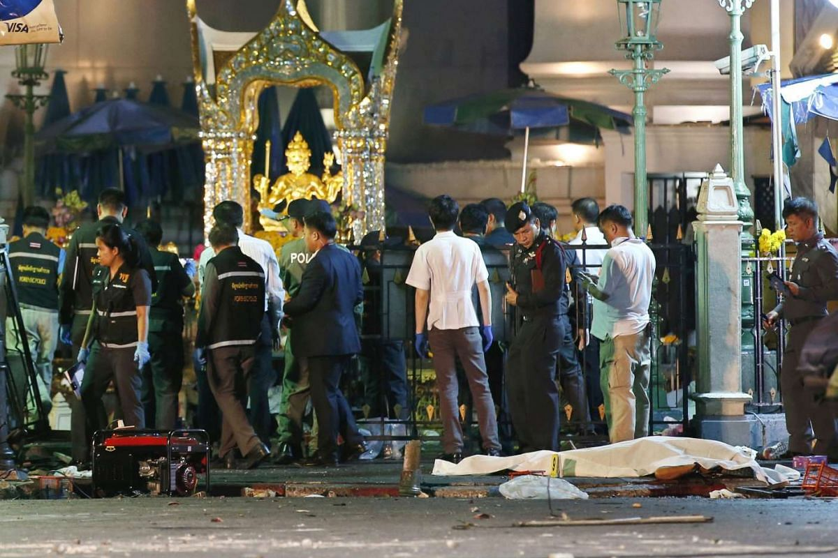 The covered body of victim (right) lies on the ground as Thai police officers inspect a blast scene after an explosion near Erawan Shrine in central of Bangkok, Thailand, Aug 17, 2015.