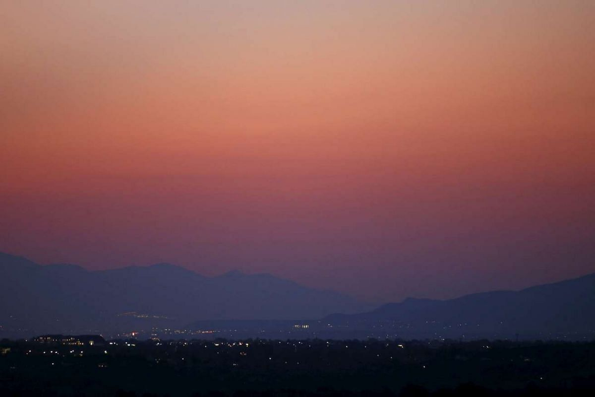 Smoke and haze from the Northern California wildfires and other major wildfires across the Western US fills the skies as the sun sets over the southern Salt Lake Valley, outside Salt Lake City, Utah on Aug 17, 2015. The US Army has been asked to send