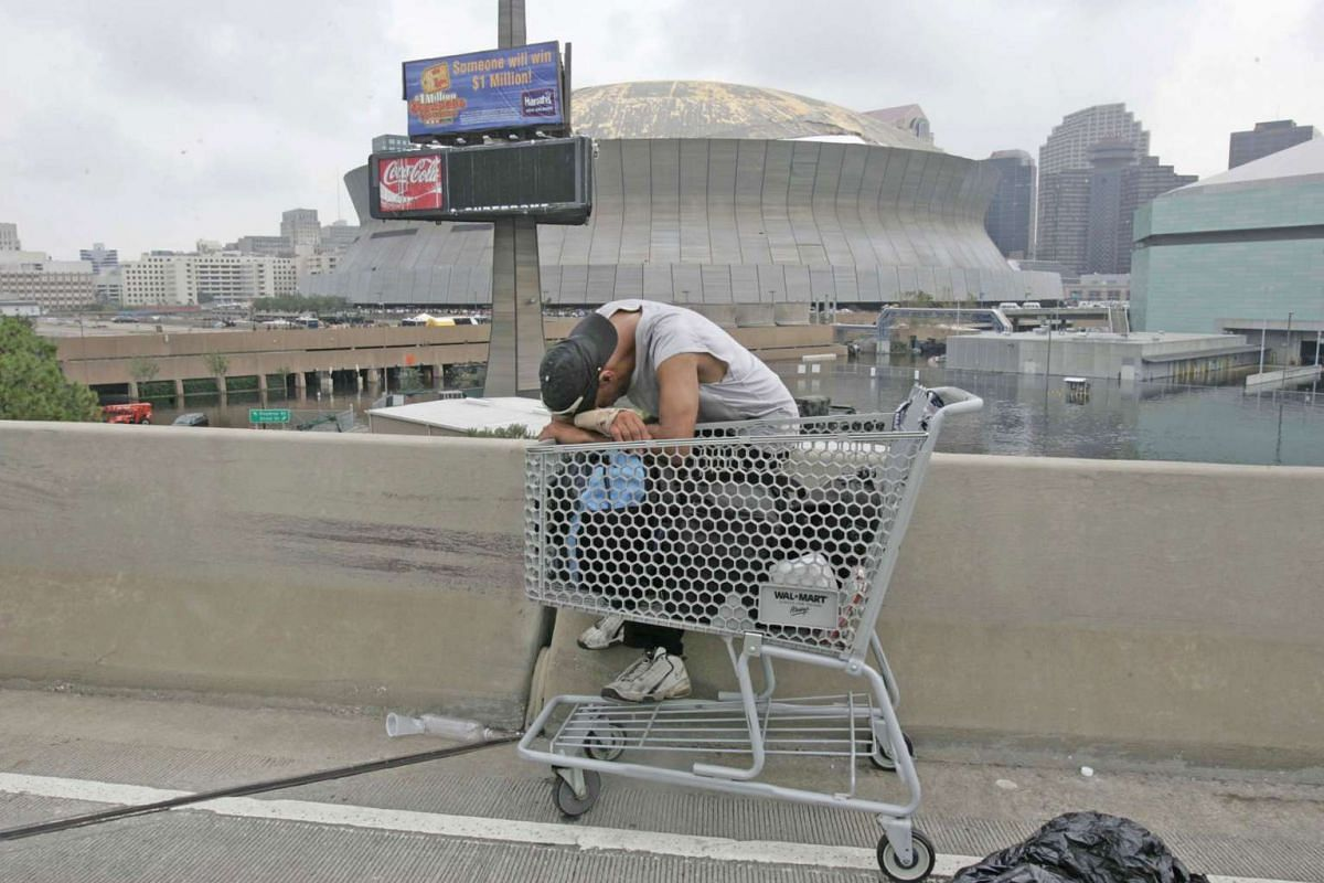 A file picture taken on Sept 1, 2005, showing a man with his head on a shopping cart across from the Superdome in New Orleans, Louisiana, in the aftermath of Hurricane Katrina.