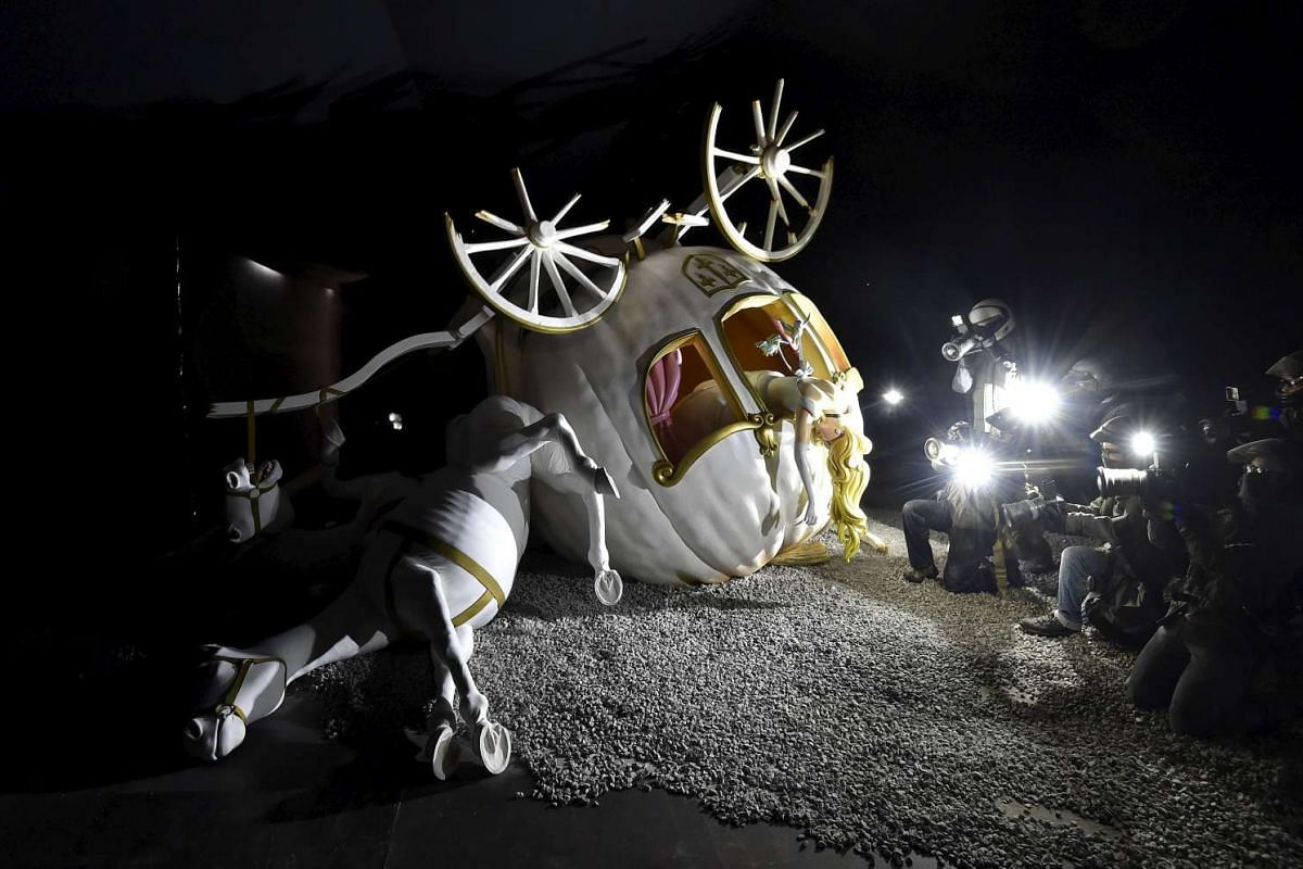 A sculpture featuring a dead Cinderella in a crashed pumpkin carriage, surrounded by paparazzi.