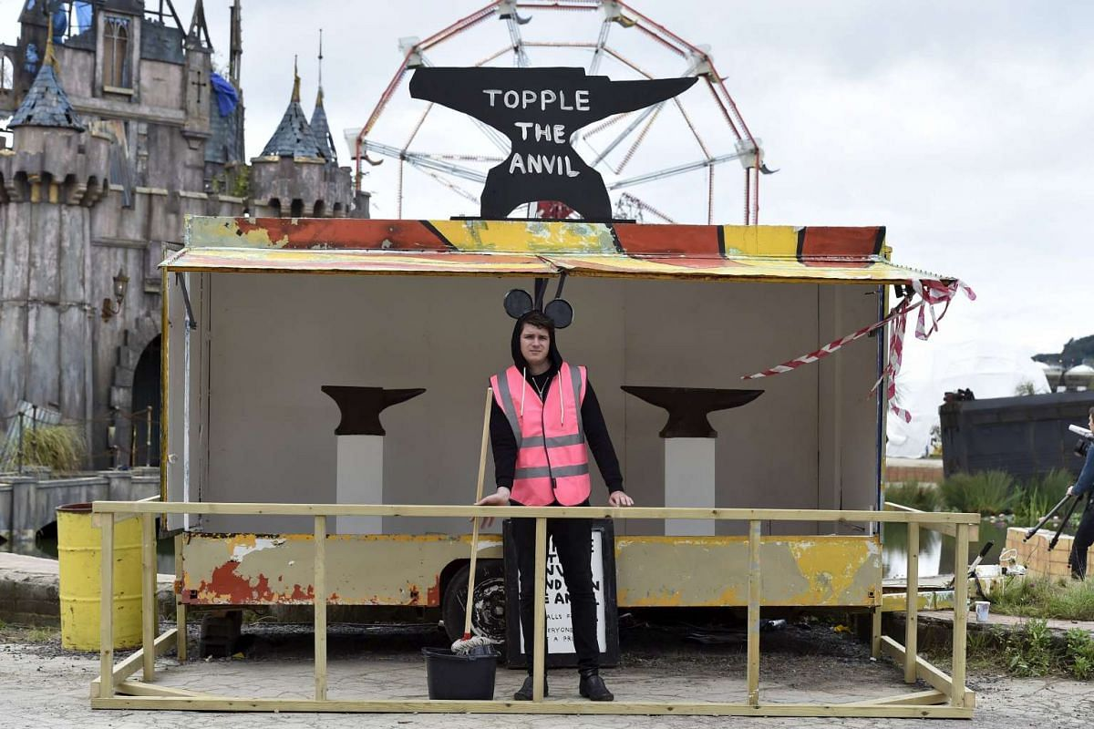 A performer standing at a game booth in Dismaland.