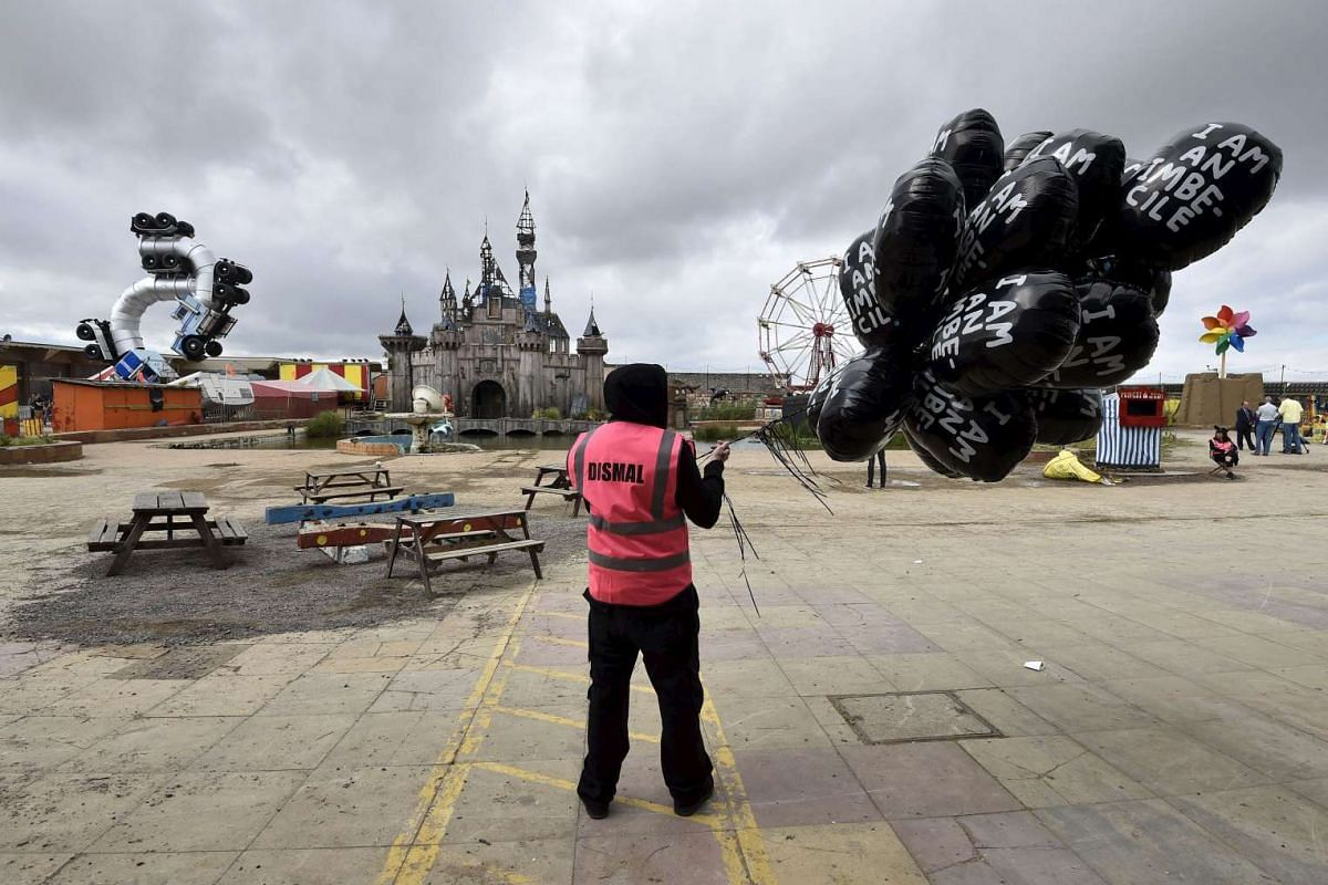 A performer holding a bunch of balloons at Dismaland.