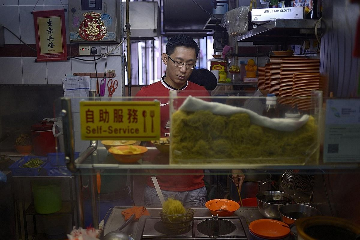 Mr Sunny Swee helping out at his mother's noodle stall at a coffee shop in Bukit Batok. Besides attending school and helping at the stall, he also tutors on a part-time basis, attends church on weekends, and volunteers at self-help group Beacon of Li