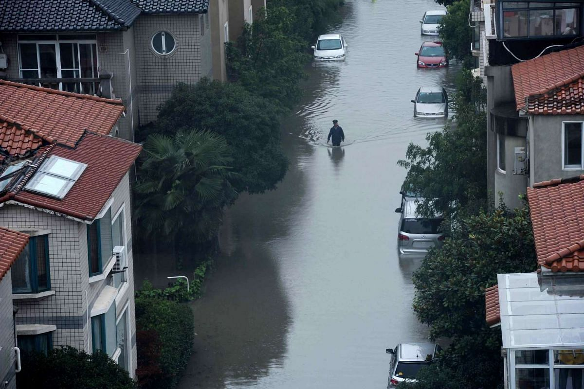 A security guard checks the surroundings in a flooded residential area after strong rains hit Shanghai, China, on Aug 24, 2015. Heavy rains brought by a cold front and enhanced by passing Typhoon Goni, currently near Japan's Okinawa islands, brought