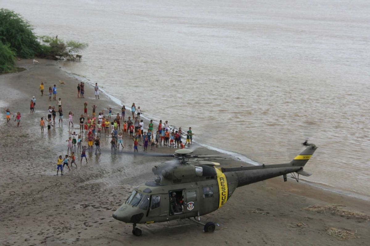 Residents wave after the distribution of relief goods by members of the Philippine Air Force after their town was battered by Typhoon Goni, known locally as Typhoon Ineng, at Santa Ilocos Sur province, north of Manila, on Aug 24, 2015.