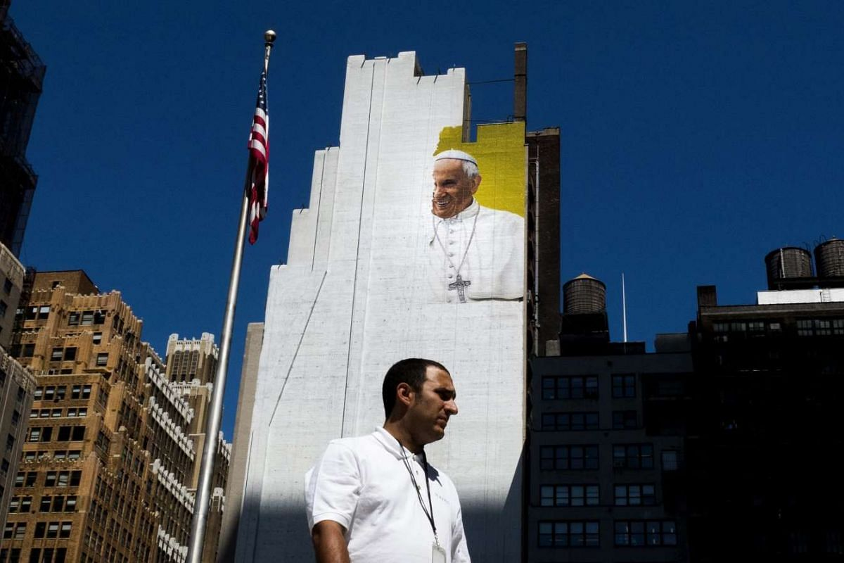 A man walking in front of an unfinished mural of Pope Francis in New York, New York. The mural is being painted in preparation for the Pope's visit to the United States, including New York, Philadelphia and Washington DC, in September 2015.