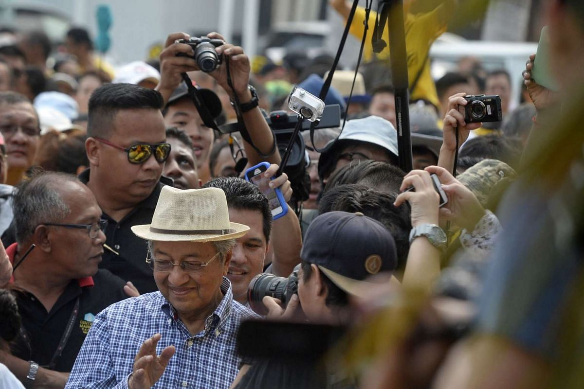 Former Malaysian Prime Minister Mahathir Mohamad (in hat and blue checked shirt) is mobbed by Bersih 4.0 protesters after speaking to the media in front of Central Market in Kuala Lumpur on Aug 30, 2015.
