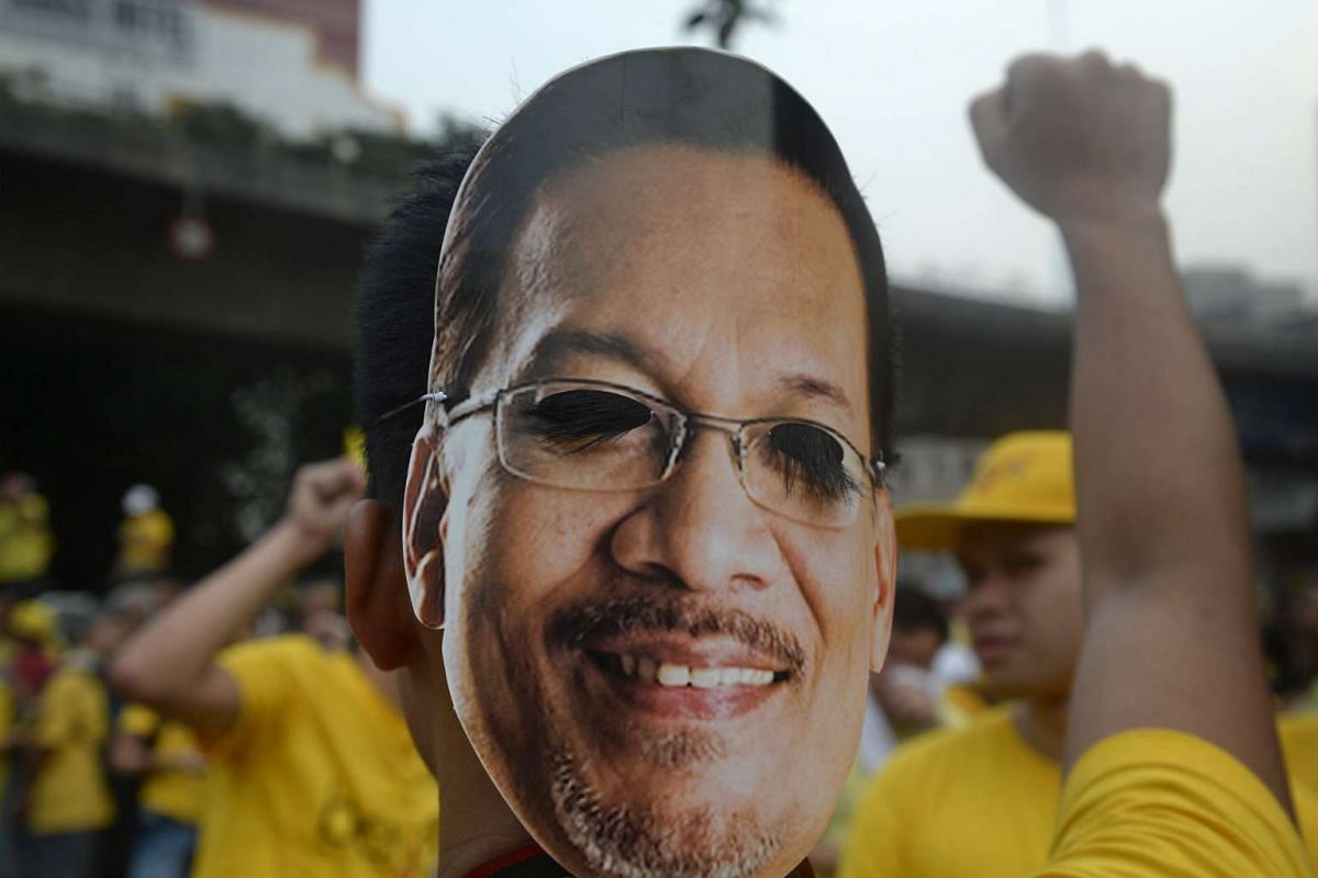 A protester wearing a mask of opposition leader Anwar Ibrahim raises his fist in the air at Merdeka Square on Aug 30, 2015.