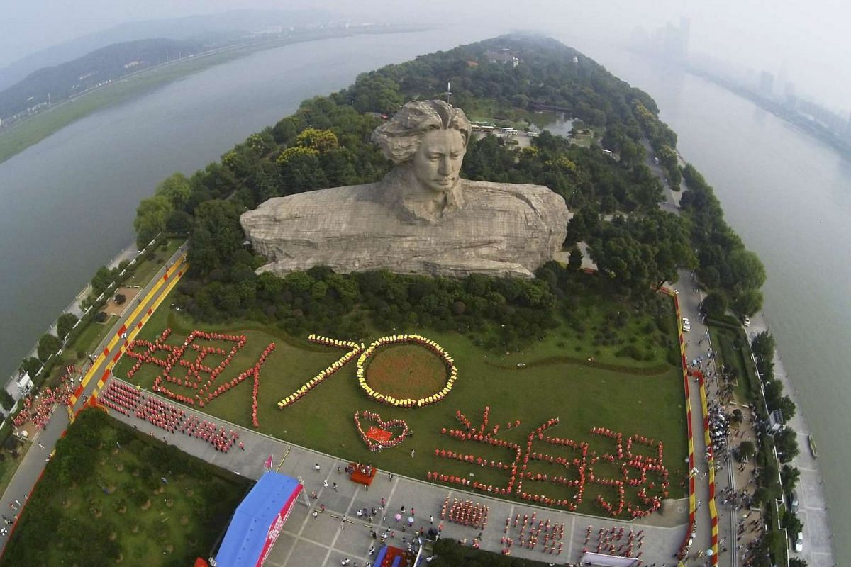 "Participants form the figure ""70"" and the Chinese characters ""The Chinese people shall strive to become stronger"" in front of a statue of China's late Chairman Mao Zedong in his youth, during an event to celebrate the 70th anniversary of the end of W"