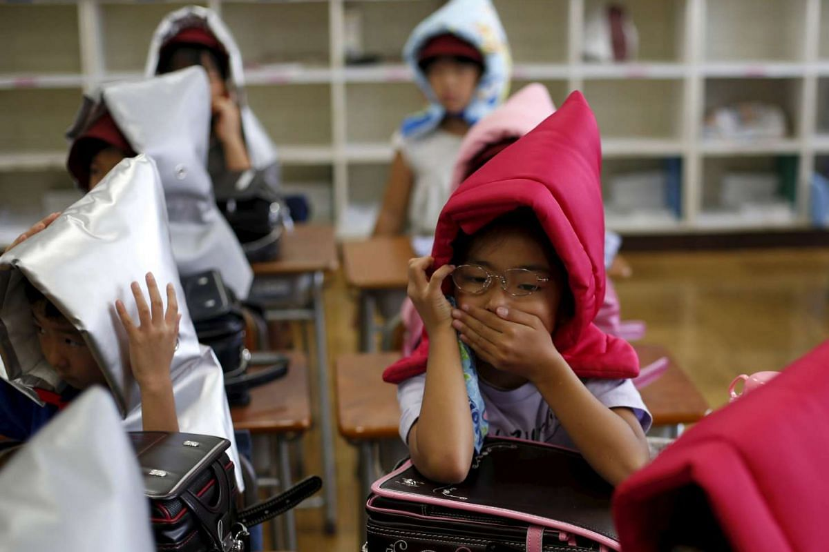 Schoolchildren wearing padded hoods to protect them from falling debris during an earthquake simulation exercise at an elementary school in Tokyo on Sept 1, 2015. The annual exercise is held nationwide on the anniversary of the 1923 Great Kanto Earth