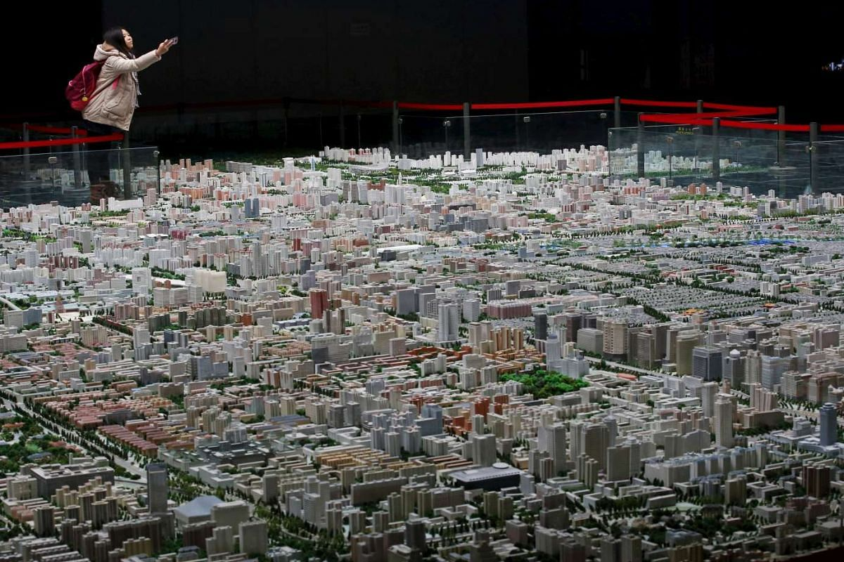 A visitor taking a photo of a model of Beijing's downtown at the Beijing Planning Exhibition Hall, a museum showcasing the achievement of the city's urban planning.