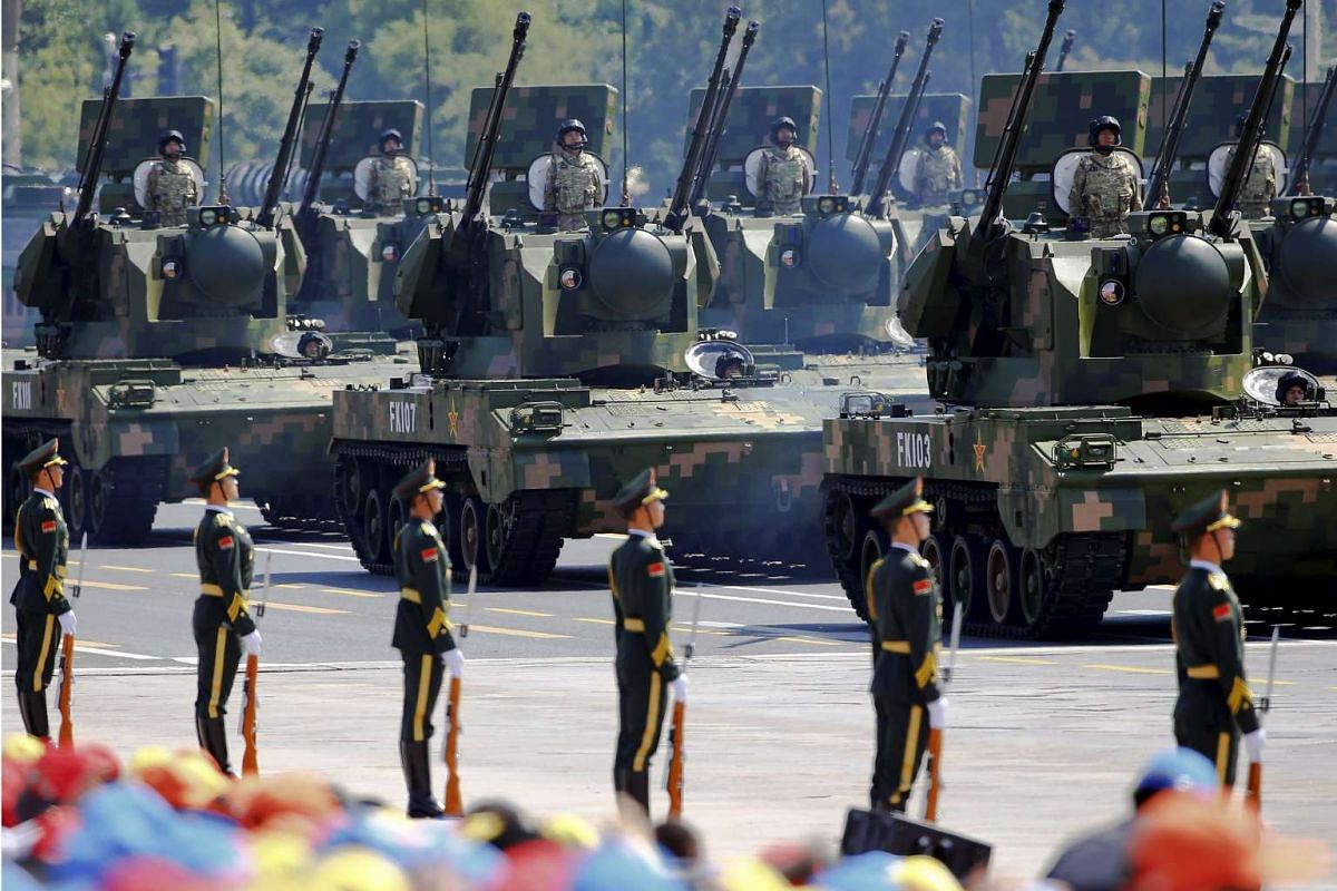 China's People's Liberation Army (PLA) soldiers on their armoured vehicles equipped with anti-aircraft artillery roll to Tiananmen Square during the military parade marking the 70th anniversary of the end of World War II, in Beijing, China, on Sept 3