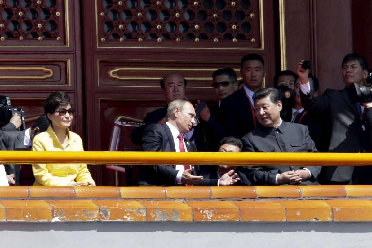 Russian President Vladimir Putin (centre) chats with China's President Xi Jinping (right) next to South Korea's President Park Geun Hye on Tiananmen Gate during the military parade marking the 70th anniversary of the end of World War II, in Beijing,