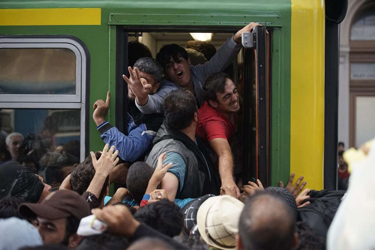 Migrants board a train at Keleti Railway Station, in Budapest, Hungary, 3 September 2015. The migrants were removed from the train by police in Bicske, 35 kms west of Budapest, in order for them to be registered at a reception center. PHOTO: EPA / ZO