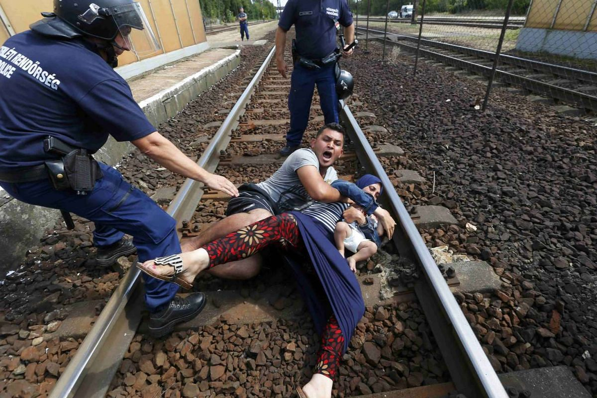 Hungarian policemen stand by the family of migrants as they wanted to run away at the railway station in the town of Bicske, Hungary, September 3, 2015. A camp for refugees and asylum seekers is located in Bicske. PHOTO: REUTERS / LASZLO BALOGH