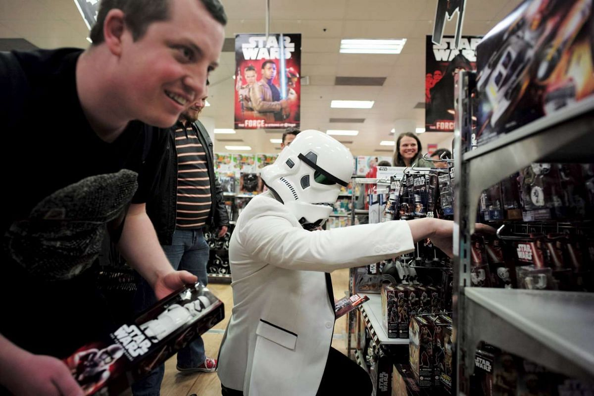A shopper wearing an Imperial Stormtrooper helmet picks new toys from the upcoming film 'Star Wars: The Force Awakens' on 'Force Friday', just after midnight on 'Force Friday' in Sydney, September 4, 2015. REUTERS / JASON REED