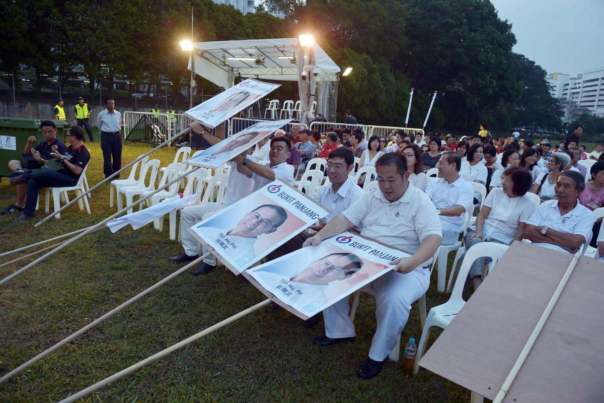 PAP supporters are their signs before the start of Bukit Panjang rally at the field in front of Blk 136 Petir Road, on Sept 5. 2015.