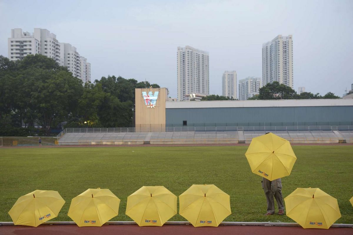 A volunteer with Reform Party arranges the party umbrellas for sale prior to the start of the rally at Clementi Stadium on Sept 5, 2015.