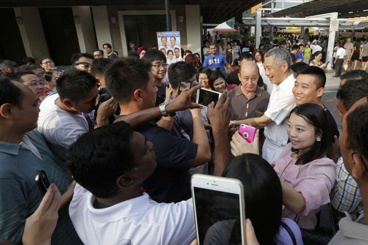 Prime Minister Lee Hsien Loong is surrounded by members of the public who want to get photographs taken with him outside Hougang MRT station as he goes on a walkabout with the People's Action Party candidates for Aljunied GRC - Yeo Guat Kwang, Victor