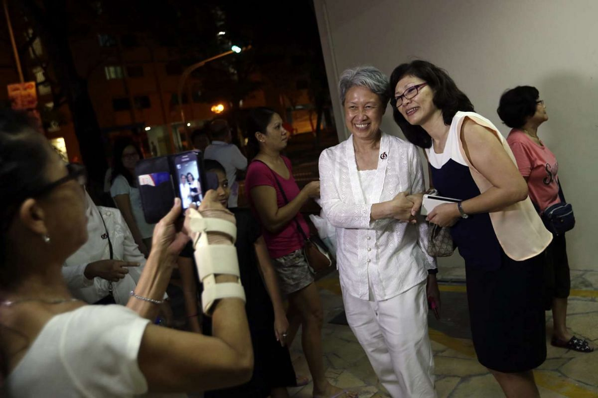 Members of the public take photographs with Madam Ho Ching, who was accompanying Prime Minister Lee Hsien Loong as he goes on a walkabout with the People's Action Party candidates for Aljunied GRC - Yeo Guat Kwang, Victor Lye, Chua Eng Leong, K. Mur
