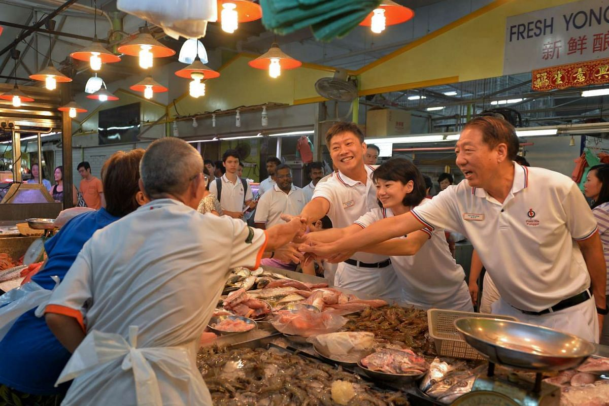 PAP Pasir Ris Punggol GRC candidates (from right) DPM Teo Chee Hean, Sun Xueling and Ng Chee Meng meeting stallholders at the wet market in Punggol Plaza on Sept 6, 2015.