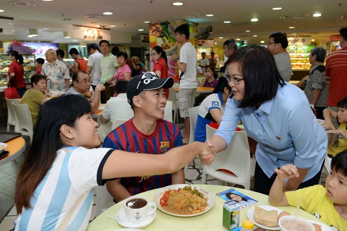 Candidate for Punggol East SMC Lee Li Lian shaking hands with members of a family having their breakfast at a food court in Rivervale Plaza on Sunday morning.