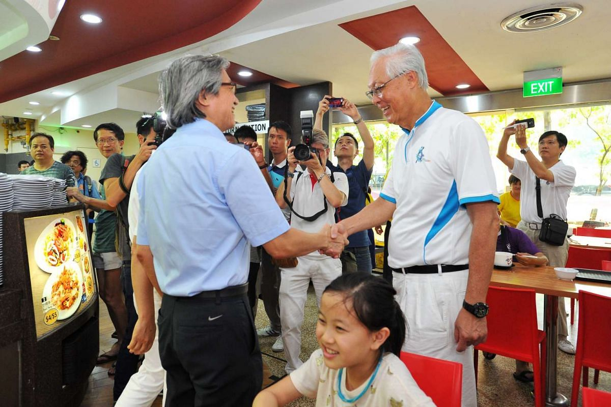 Workers' Party Aljunied GRC candidate Chen Show Mao (left) shaking hands with ESM Goh Chok Tong at the Hougang Central food court on Sept 6, 2015.
