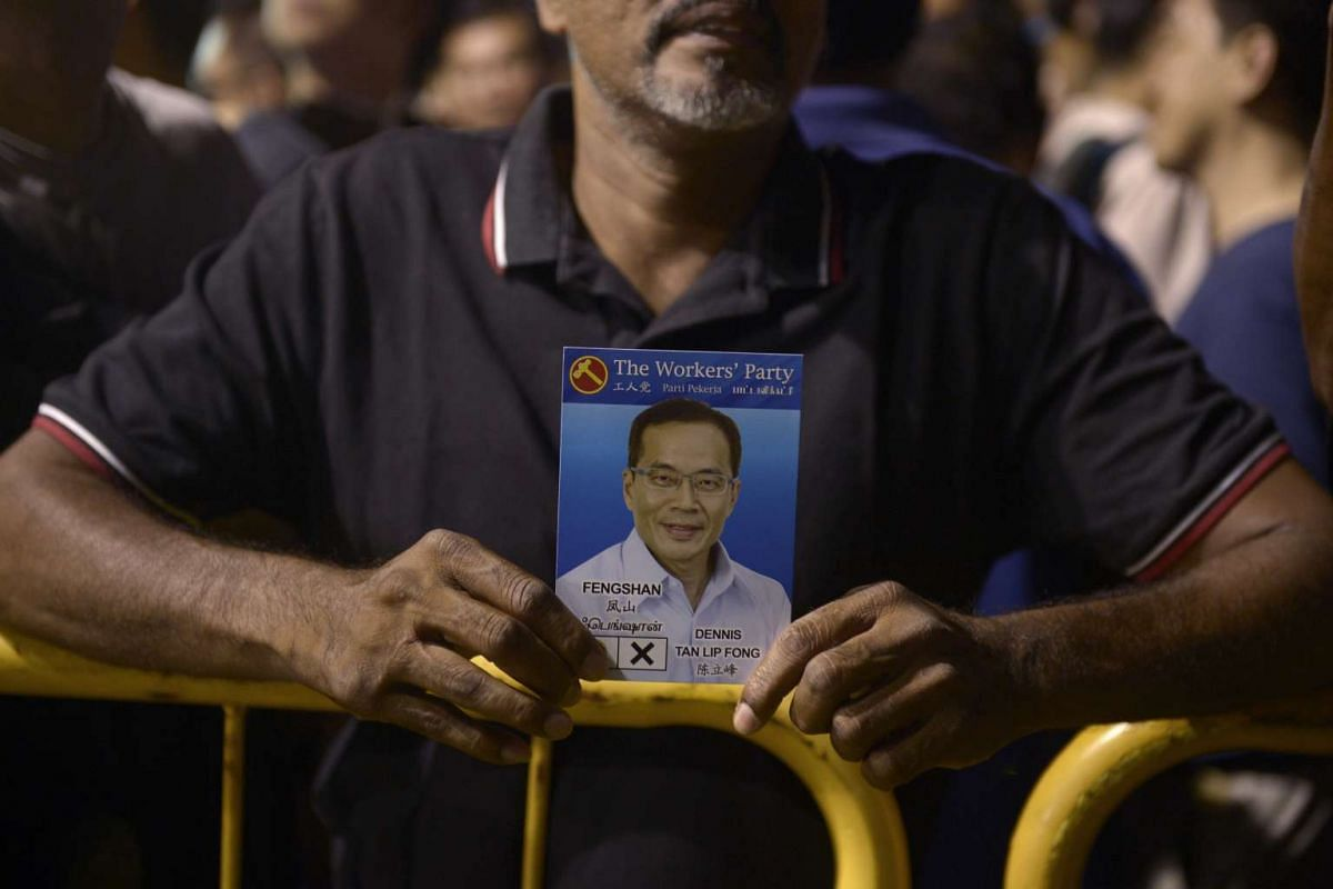 A supporter holding up a card with a picture of WP's Fengshan SMC candidate Dennis Tan on it.