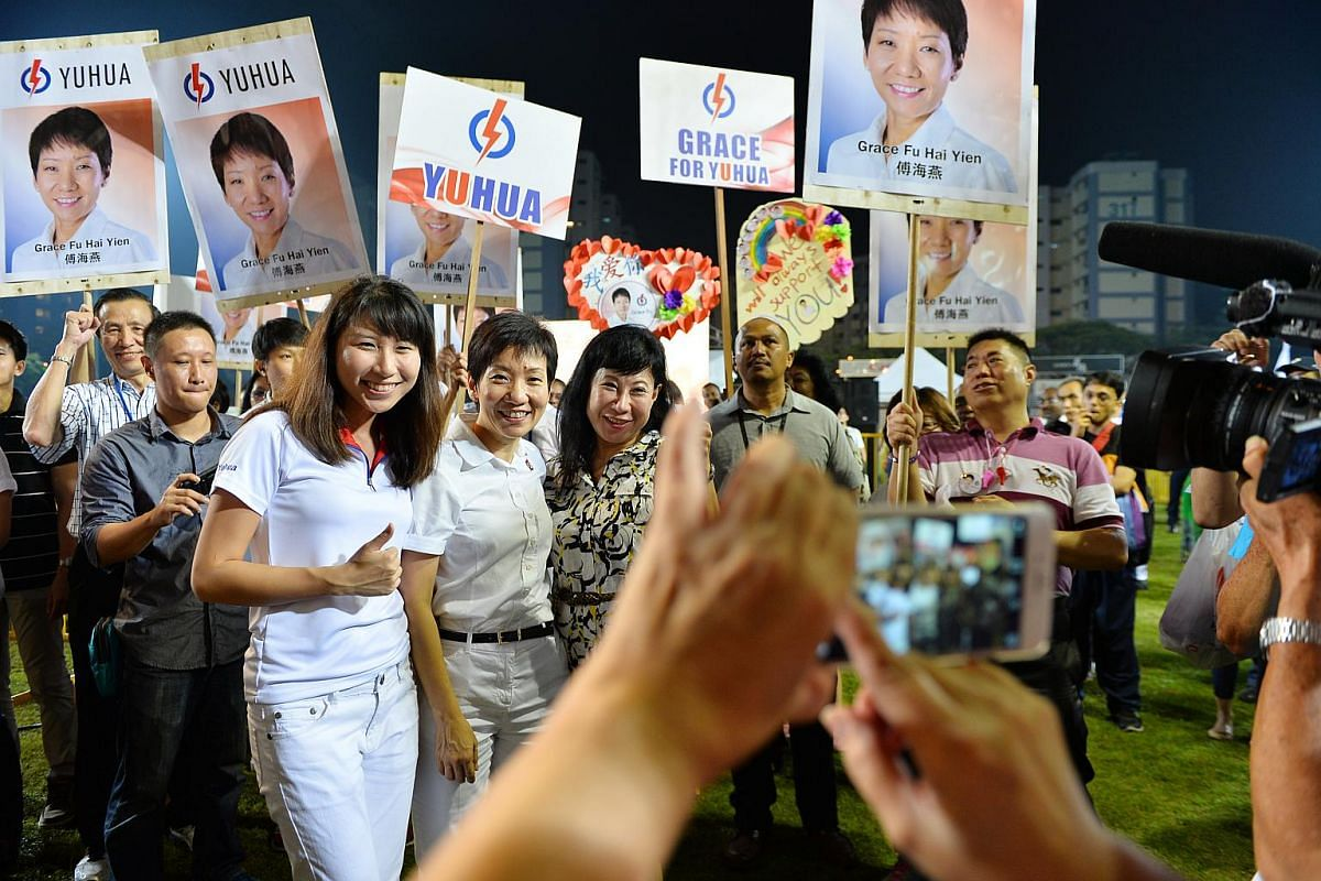 The PAP candidate for Yuhua SMC, Ms Grace Fu (front row, centre), taking a picture with her supporters at the party's rally in Jurong East Stadium.