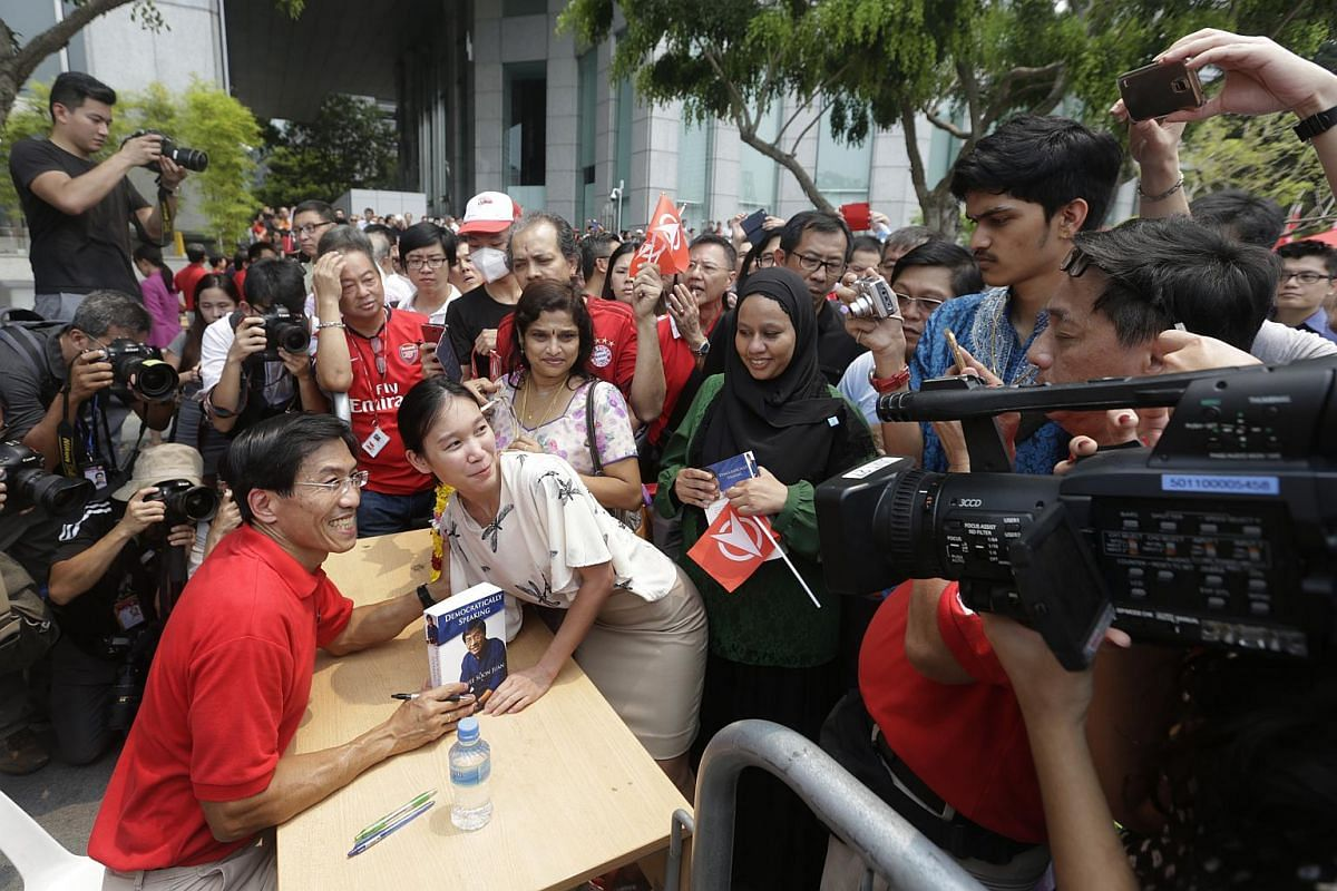 Singapore Democratic Party chief Chee Soon Juan having a photo taken with a member of the public during his book signing after a lunchtime rally at the UOB Plaza promenade on Sept 7, 2015.