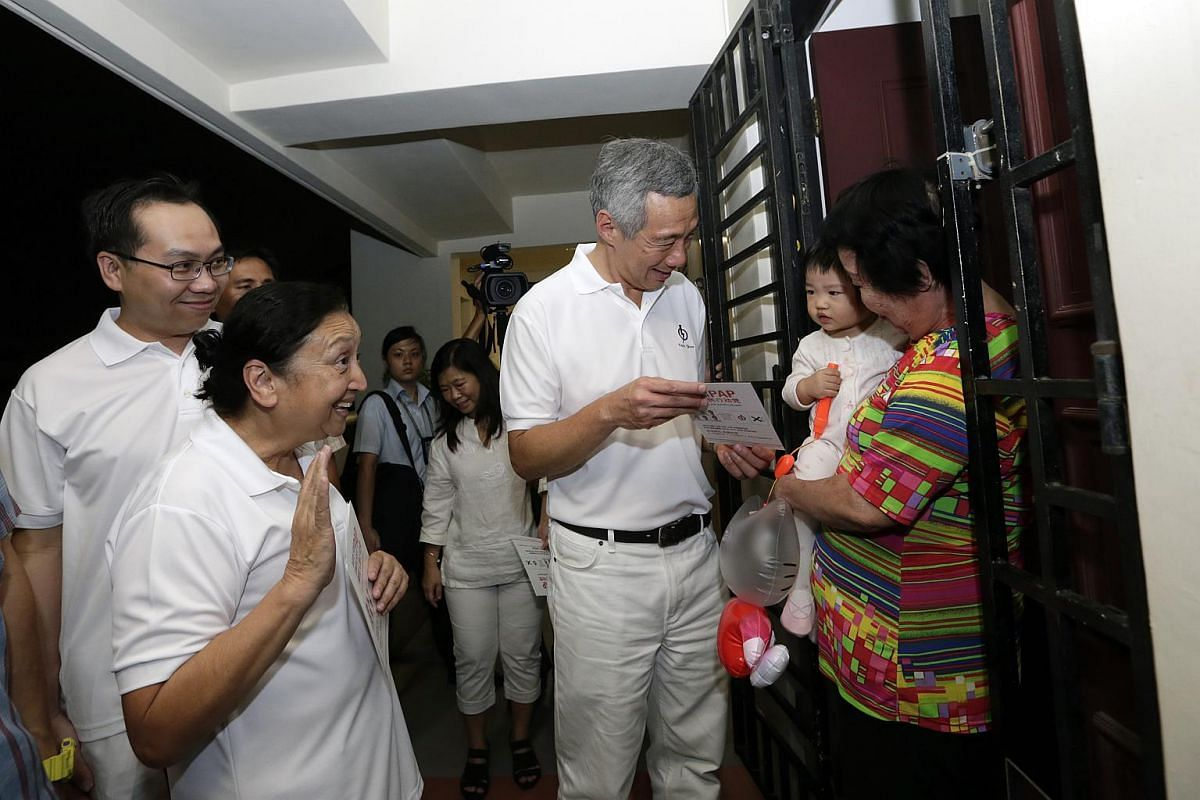 People's Action Party secretary-general Lee Hsien Loong (centre) passing a campaign pamphlet to one-year-old Hing Hze Xuan, who is being carried by her grandmother, Madam Koh Geok Huay, 75, in  Ang Mo Kio Street 31 on Sep 7, 2015.
