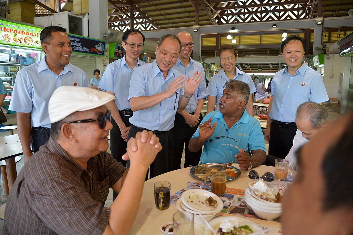 Workers' Party secretary-general Low Thia Kiang (centre, gesturing) with the party's Marine Parade GRC candidates (from left) Firuz Khan, Yee Jenn Jong, Terrence Tan, He Ting Ru and Dylan Ng speaking with residents at the Geylang Serai market.