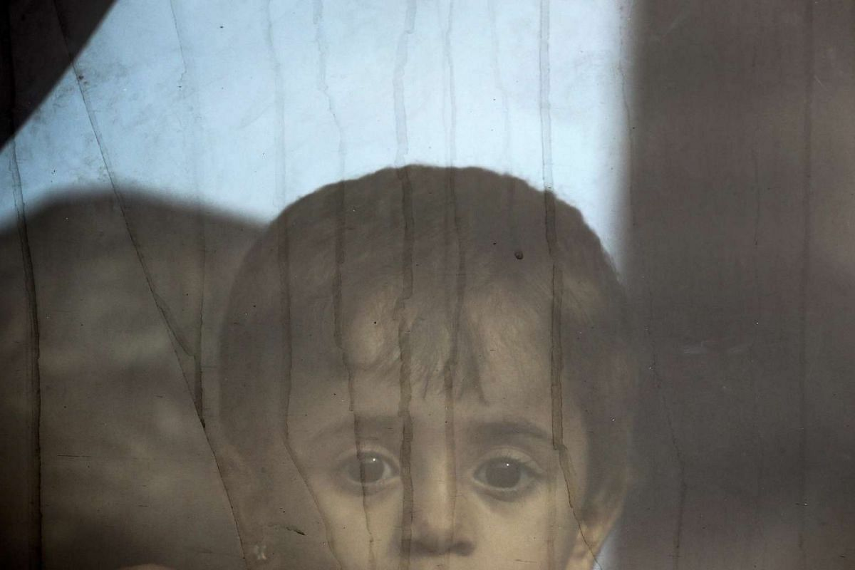 A Syrian refugee girl looking out of the window of a bus after arriving at Greece's border with Macedonia, near the Greek village of Idomeni, on Sept 8, 2015. PHOTO: REUTERS / YANNIS BEHRAKIS