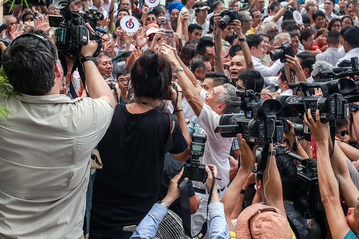 Prime Minister Lee Hsien Loong takes a picture of the crowd at the PAP lunchtime rally before leaving on Sept 8, 2015.