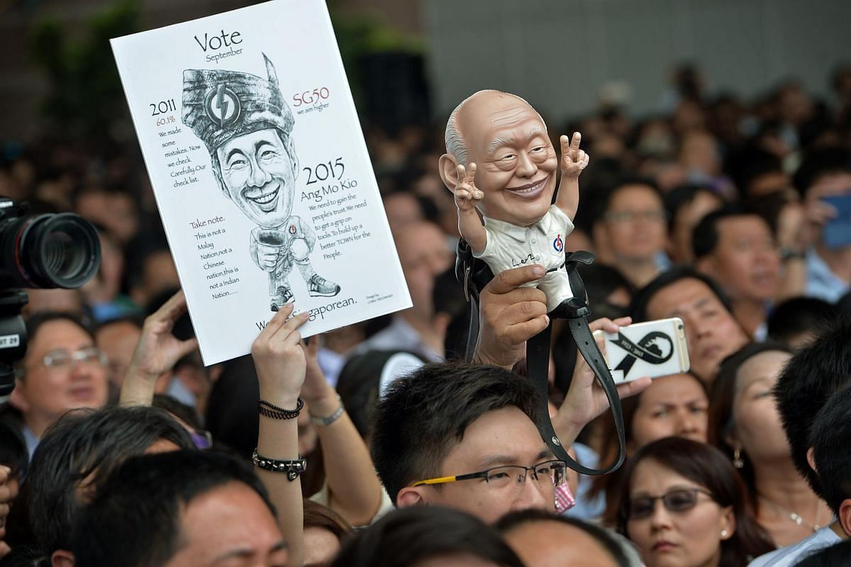 Supporters holding up a drawing of Prime Minister Lee Hsien Loong and a figurine of founding prime minister Lee Kuan Yew at a People's Action Party (PAP) lunchtime rally held at the Promenade area beside UOB Plaza on Sept 8, 2015.