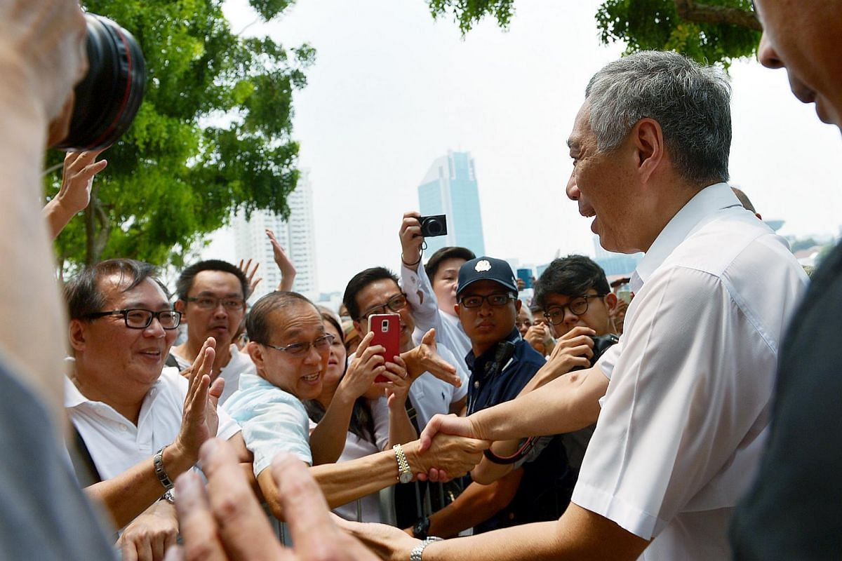 Some members of the crowd eager to catch a snapshot of Prime Minister Lee Hsien Loong and shake his hands at a People's Action Party (PAP) lunchtime rally held at the Promenade area beside UOB Plaza on Sept 8, 2015.