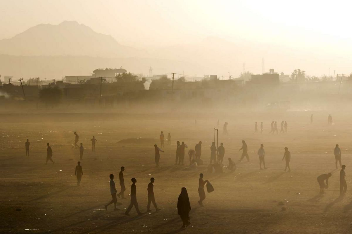 People walking on an open field as the sun rises in Kabul, Afghanistan, on Sept 9, 2015. PHOTO: REUTERS/AHMAD MASOOD