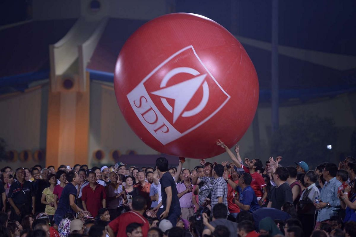 Supporters of the Singapore Democratic Party (SDP) passing on a giant inflatable ball thrown into the crowd at the party's rally at Woodlands Stadium.